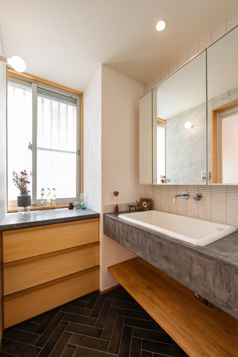 洗面はモールテックスを用いたカウンター造作家具やいぶし黒色のタイルでシックな仕上がり