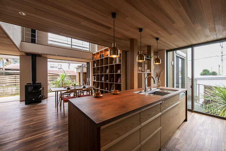 木製の大開口サッシの先にある南庭や葉山の海を眺めながら料理できるアイランド型対面キッチン
