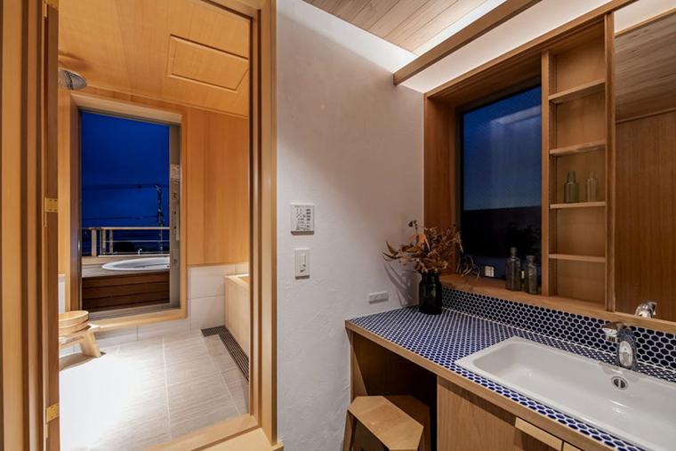 大きな収納付鏡戸のある 造作洗面カウンターから桧風呂を通り屋上テラスへ続く