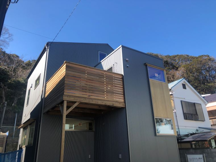 カラーガルバリウム鋼板と板張りのシンプルな外観に2階デッキとルーフデッキのある楽しい家