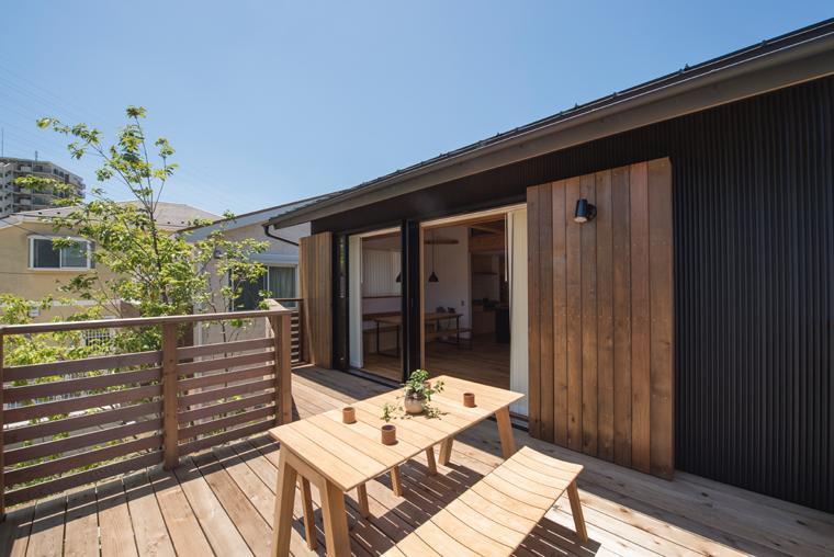 広い2階デッキに木製のテラスセットを置いた開放的なプライベート空間。
