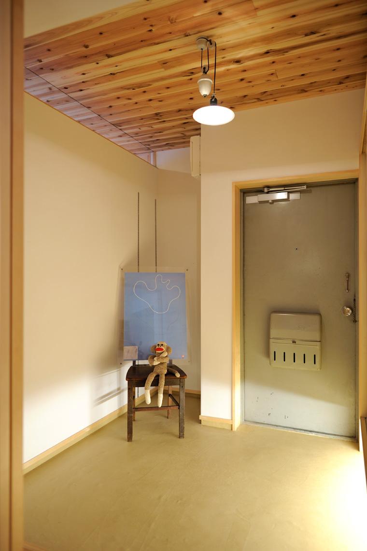 写真③ 暗く狭かった玄関に視線の抜けをつくり、明かりを取り入れて自転車やベビーカーを置ける広い玄関土間に。壁は漆黒塗、土間仕上げは応用珪藻土を採用。
