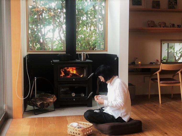体の芯から暖まる薪ストーブは、揺らめく炎と陽射しが降り注ぐ大きな窓の先に見える雑木の庭を眺めつつ、手編みをするぜいたくなひと時。吹き抜けも下でも寒くない家じゅうが温度ムラなく暖かな高断熱高気密住宅でパッシブデザインされた設計で冬暖かい家