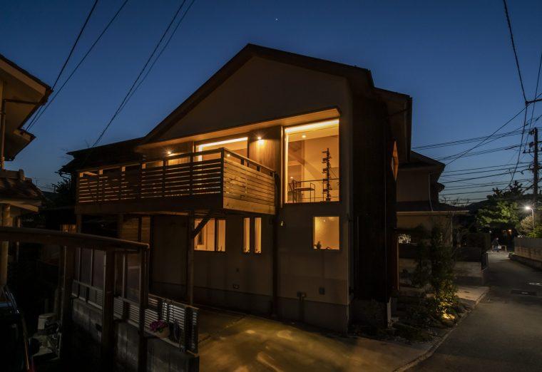 大きな二階ウッドデッキと二階の回廊が浮かんで見える夜の佇まい。