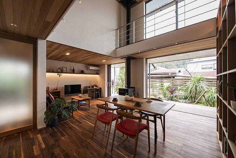 葉山町一色の「OHANA PORTO」のリビングダイニング。こちらも二ヵ所の開口を二本引き込みで全開放に。    深い軒のラナイと一体感のある空間で、豊かな暮らし方を実現しています