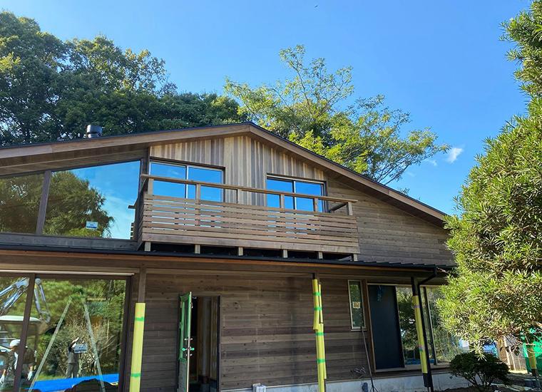 熊野の杉板貼りの外壁と、伸びやかでシンメトリックな大屋根が特徴的な外観